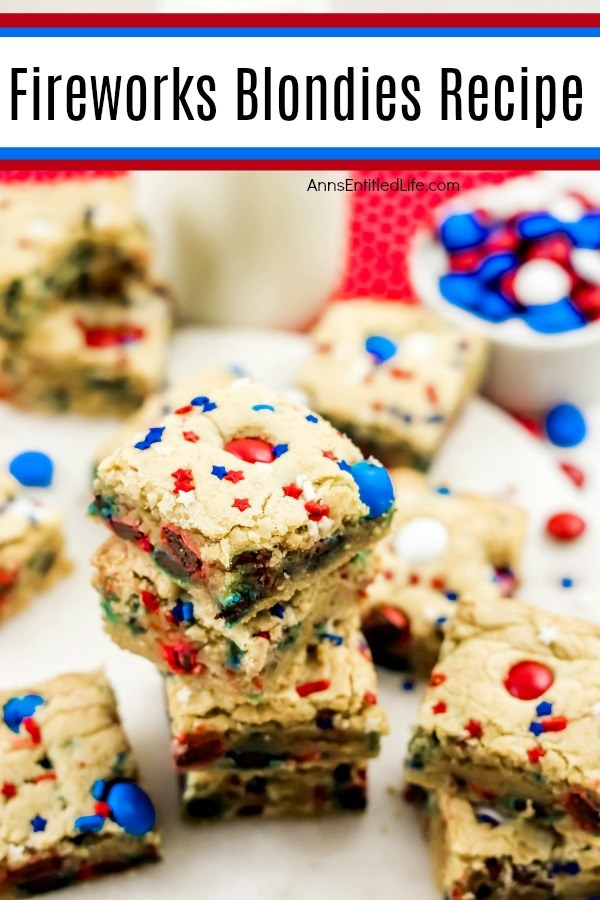 festive red, white, and blue blondies bars on a white plate, M&Ms upper right, milk glass on red polka dot napkin upper center