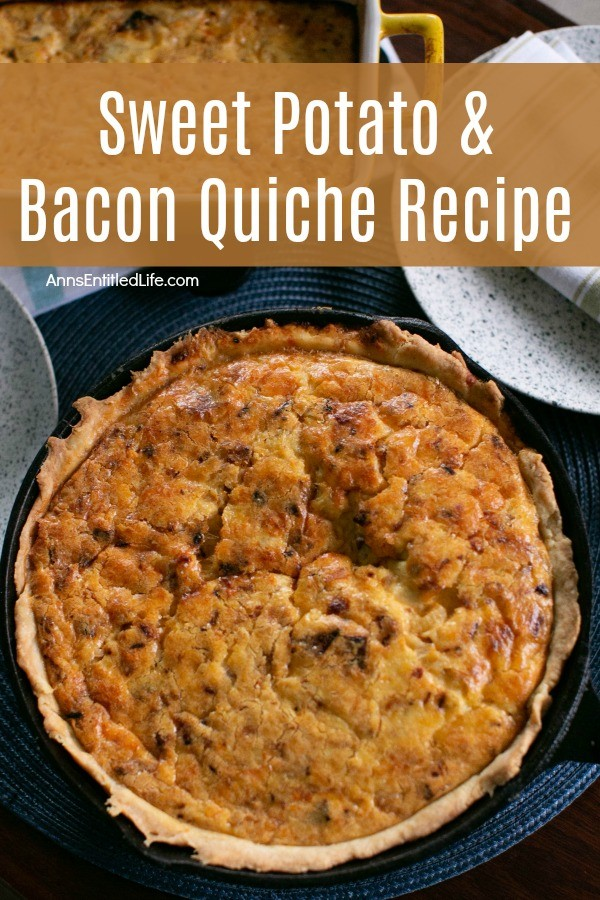 whole sweet potato and bacon quiche, in a black pan, on a blue placemat. A napkin and silverware rests to the upper right, a pan of potaties is in the upper left