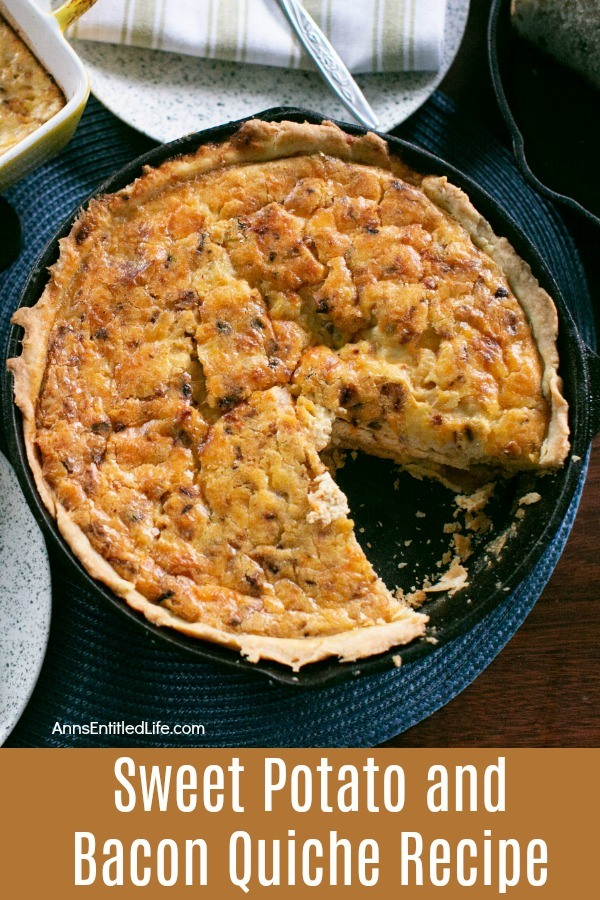 sweet potato and bacon quiche missing on slice, in a black pan, on a blue placemat. A napkin and silverware rests above the serving