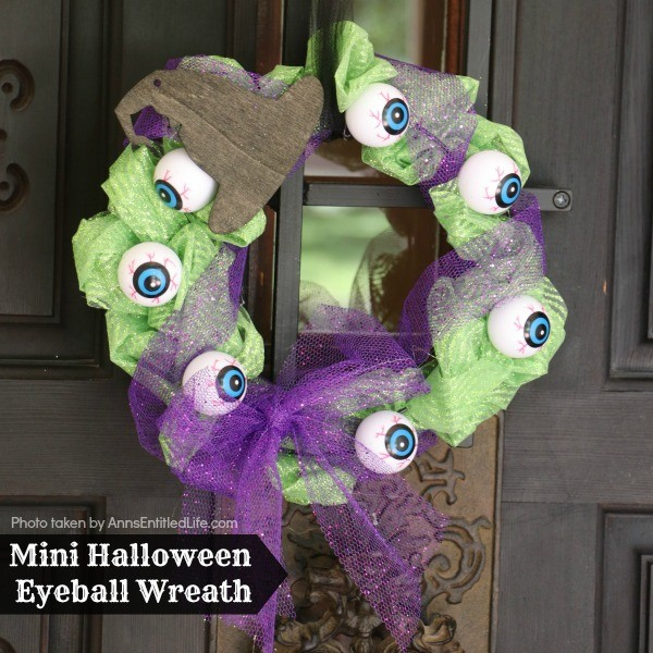 Mini Halloween Eyeball Wreath. This spooky little Halloween eyeball wreath is simple to make by following these step by step tutorial instructions. A fast Halloween decor craft, you can use these mini wreaths to decorate cabinets, desks, or as great Halloween party decor accessory.