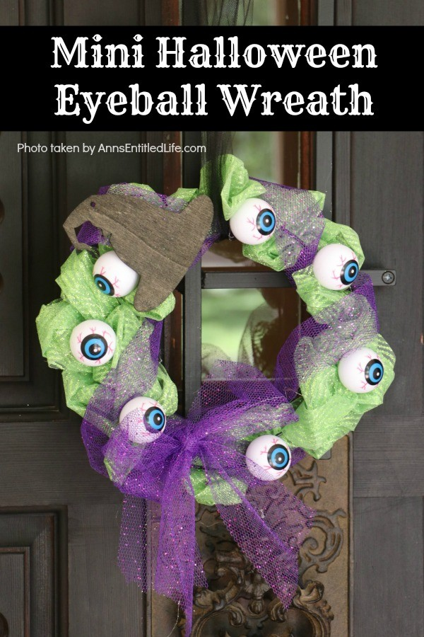 green tulle mesh wreath with purple bow and overlay, black wooden hat and hanger, hanging on a black door