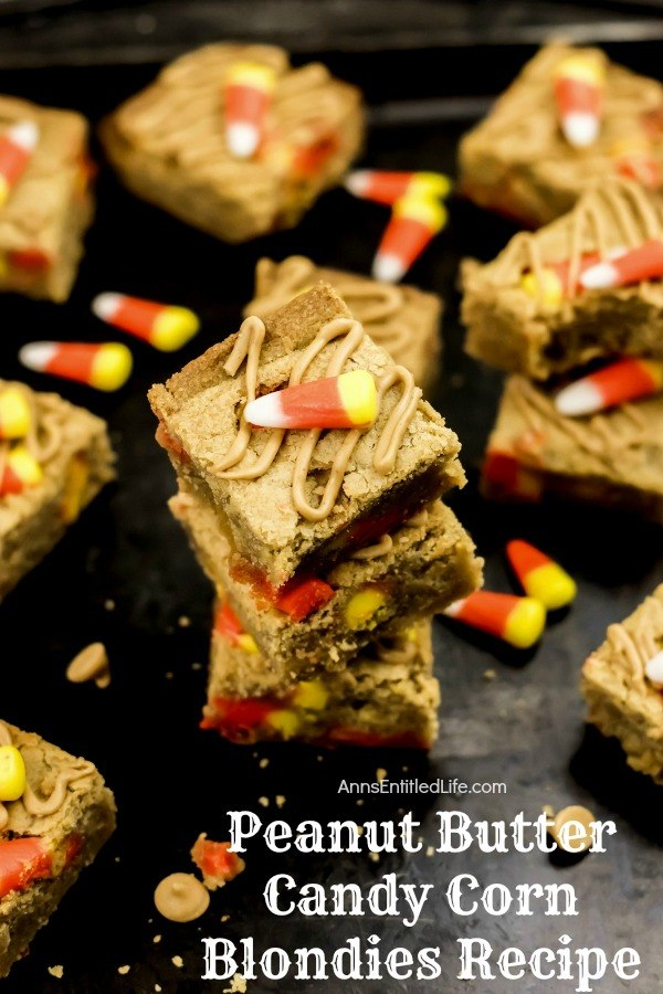 stack of peanut butter candy corn blondies on top of a black counter, dropped candy corn for garnish, and more of the blondies surrounding the stack