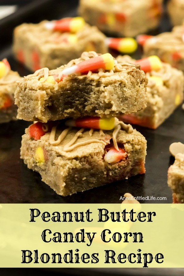 a double stack of peanut butter candy corn blondies on top of a black counter, the top blondie has a piece missing to expose the inside, dropped candy corn for garnish, and more of the blondies surrounding the stack