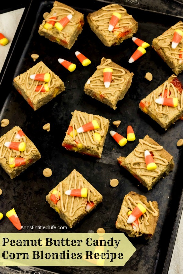 peanut butter candy corn blondies on top of a black tray, dropped candy corn and peanut butter chips for garnish