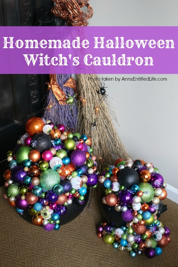 multicolored bulbs formed to immitate bubbles flowing from the cauldron base. There are two cauldrons, one large, one small. Two decorated broom are in the background, ouside on a porch