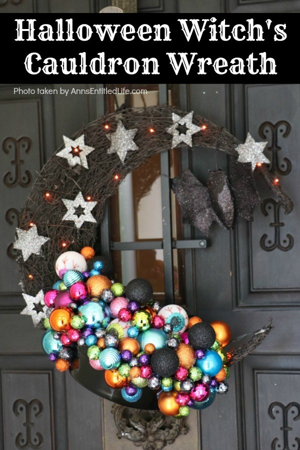 multicolored bulbs formed to imitate bubbles flowing from the cauldron attached to a half-moon black prelit wreath, hanging on a black door
