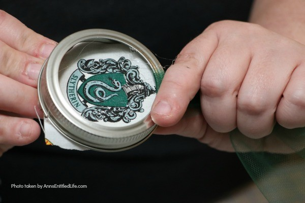 Hogwarts Mason Jar Lid Ornaments. Are you, or your children, Harry Potter fans? These easy to make Hogwarts Mason Jar Lid Ornaments come together in about 10 minutes! These are perfect for your holiday tree, to give as a gift, or for a Harry Potter or Hogwarts themed party.