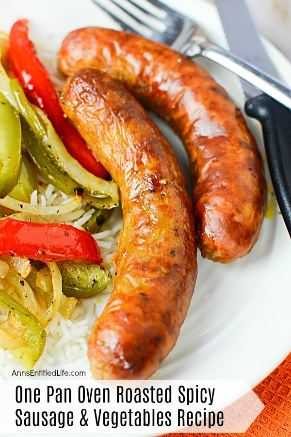 Two cooked sausages next to cooked peppers and onions on a bed of rice atop a white plate, serving utensils to the right