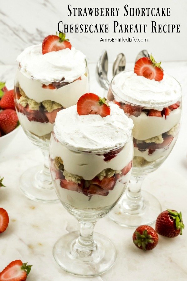 overhead view of three strawberry cheesecake partfait desserts on a white background, bowl of fresh strawberries to the left, individual strawberries on the white to the right, utensils in the  background