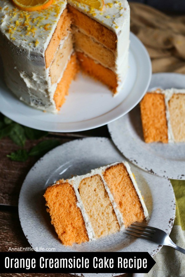 Two pieces of plated orange creamsicle cake, the remaining three-tier cake is on a white cake plate behind the pieces of served cake