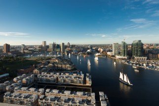 Arial color photo of Baltimore's Inner Harbor, with sailboats and the Baltimore skyline in the background.