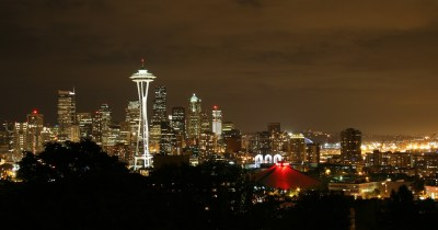A photo of the Seattle, WA, city skyline lit up at night, with a deep orange sky.