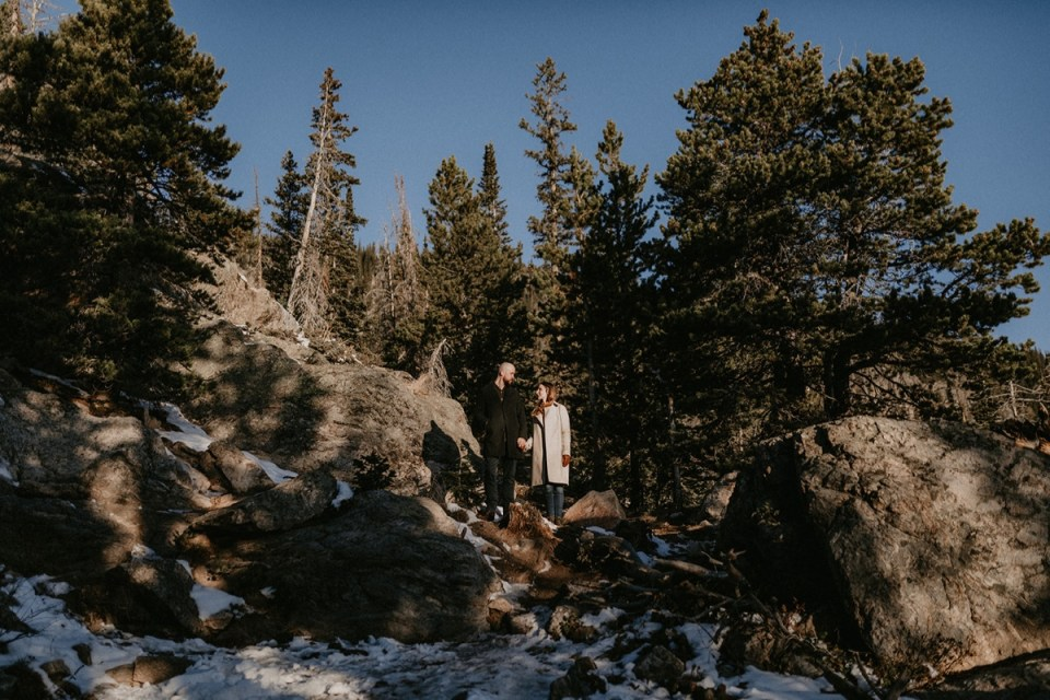 Couple holding hands in the woods during their Rocky Mountain National Park engagement photos.