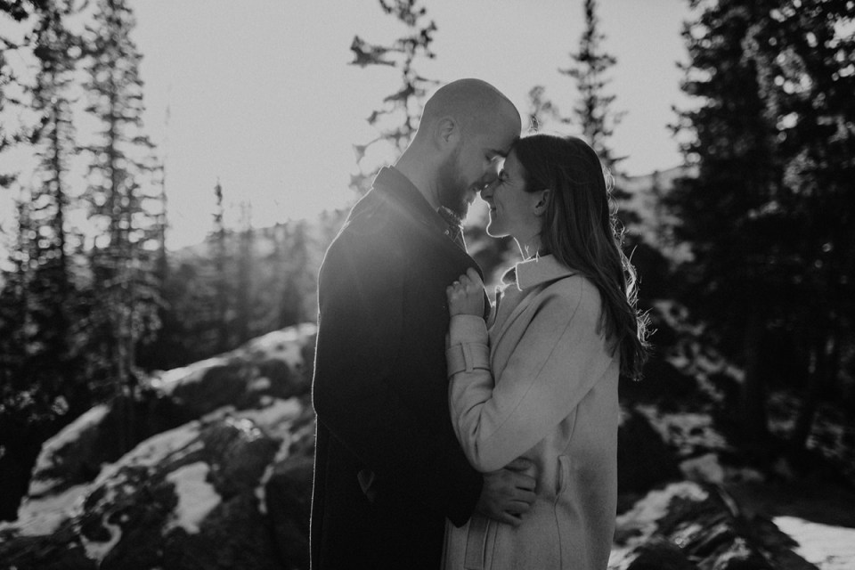Woman scrunches nose hugging her fiancé during their Rocky Mountain National Park engagement photos.
