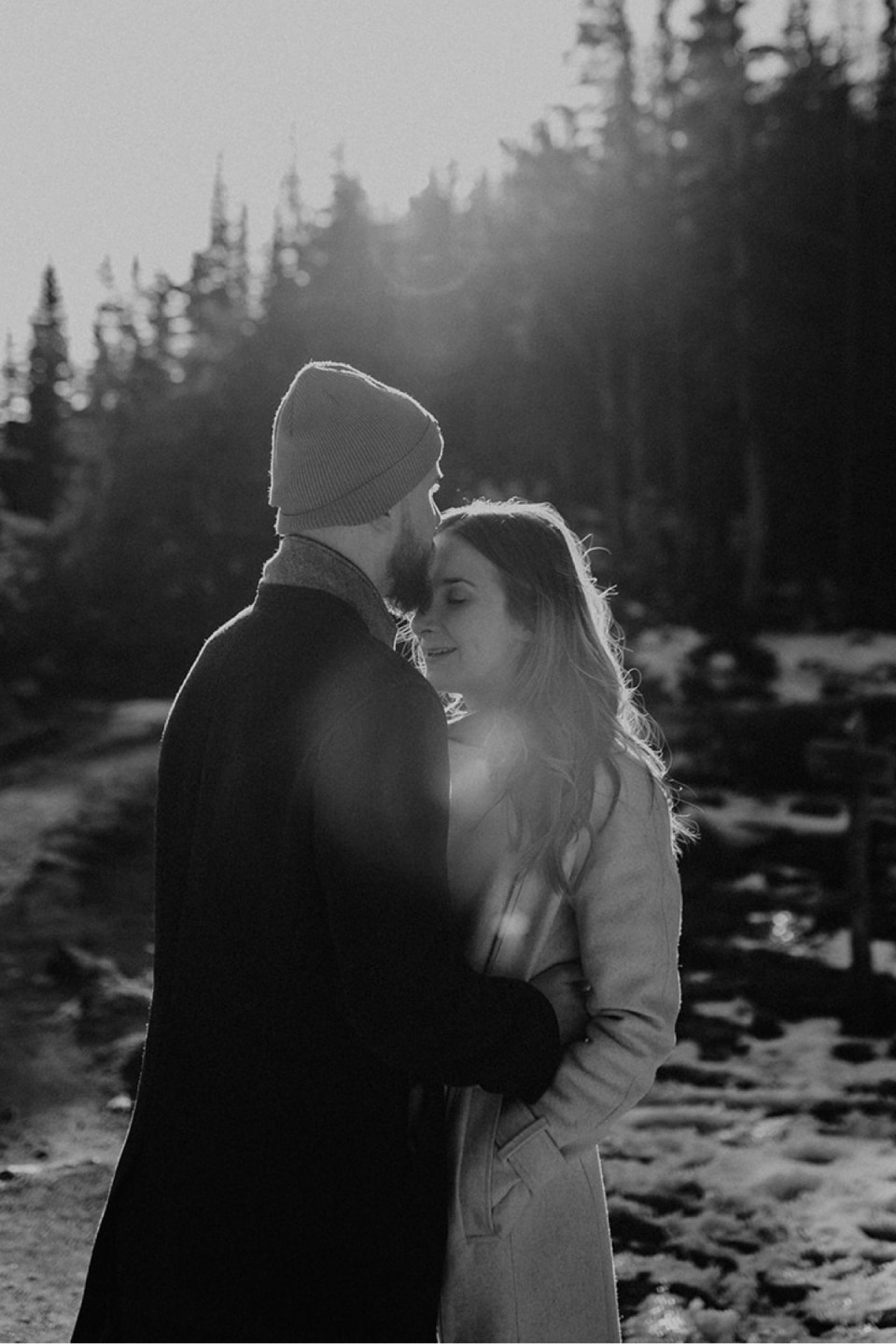 Man kissing the forehead of his fiancée during their Rocky Mountain National Park engagement photos.