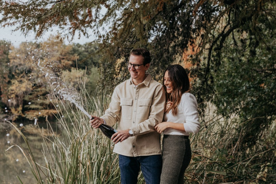 Couple celebrating by popping champagne after getting engaged.