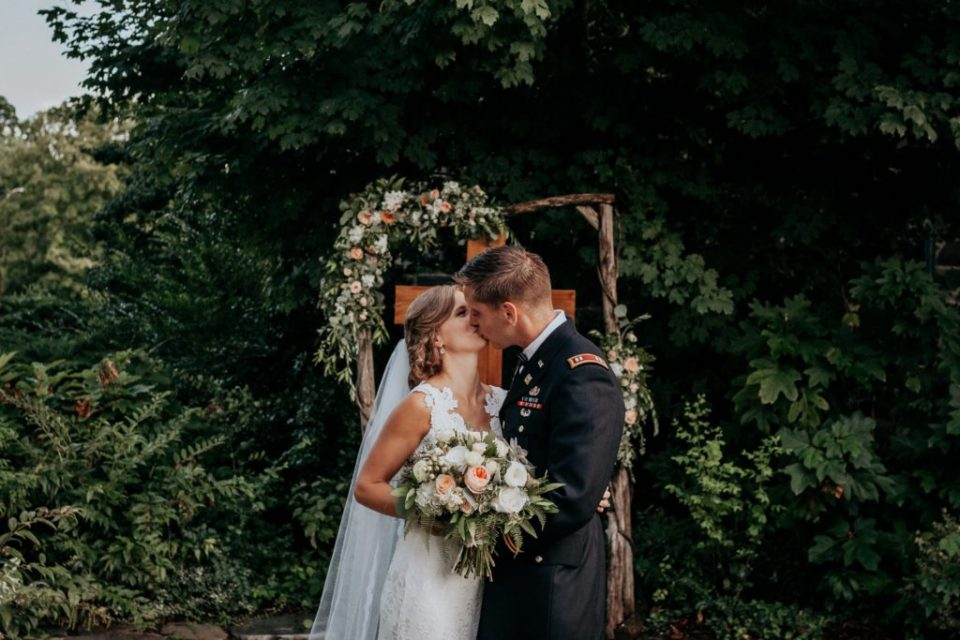 Couple kissing on their wedding day in the garden.
