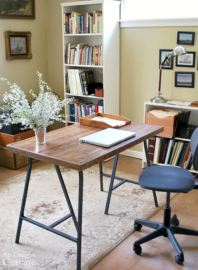 DIY desk with Ikea trestle legs and salvaged wood flooring top- an do-able tutorial for an industrial style table-desk for under $30.