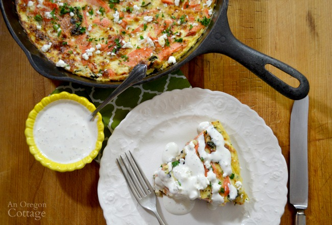Greek flavored salmon and vegetable frittata with a creamy feta sauce makes a perfect skillet weeknight meal.