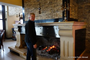 Tim warming up by a massive fireplace