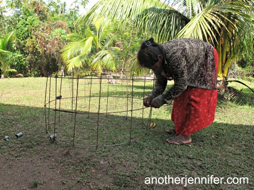 Linda, 41, building casings for a well in her village.