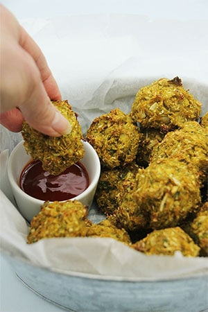 baked veggie balls being dipped