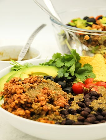 mexican bulgur bowl in white bowl with black beans, black olives, coriander, tomatoes, avocado, tortilla chips, bowl of salad and dressing in background.
