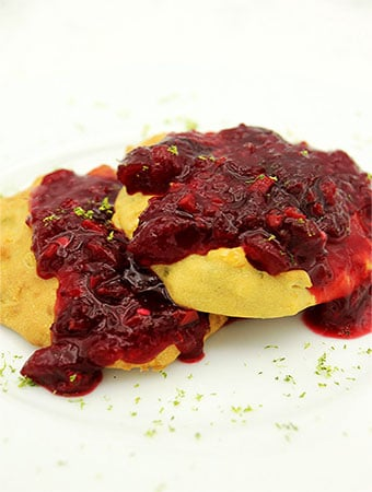Corny cakes smothered with spicy cranberry sauce on white plate with lime zest on top