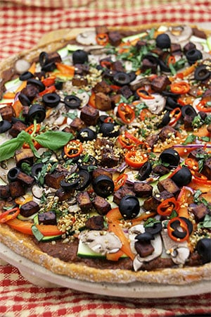 sweet potato crust pizza with black olives, smoked tofu, red peppers on red checkered cloth