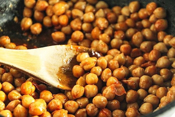 Chickpeas for buffalo chickpea bowls in cast iron pan with sauce.