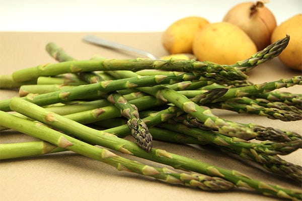 Fresh asparagus stalks on cutting board with potatoes