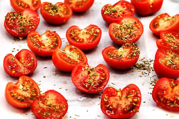 Fresh tomatoes are sliced and sprinkled with Herbs de Province for baking.