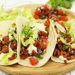 3 easy tempeh tacos on wooden plate with blue striped cloth