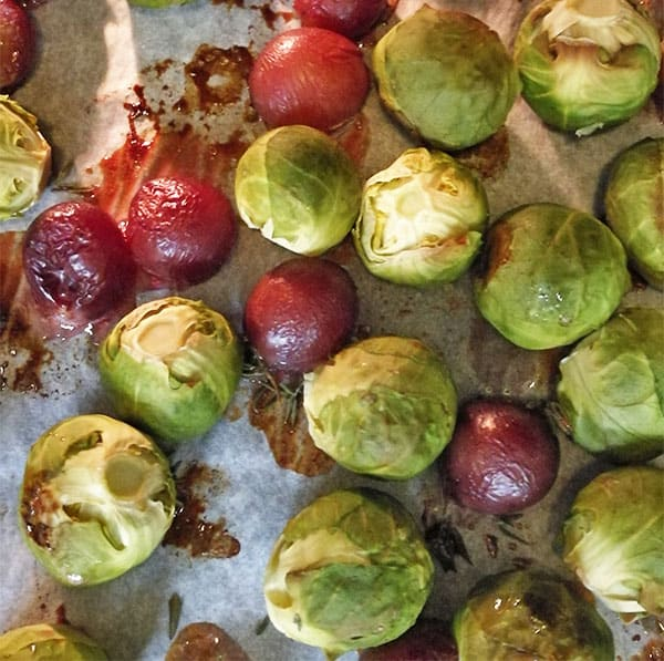 Brussels sprouts, grapes and thyme being baked on parchment paper
