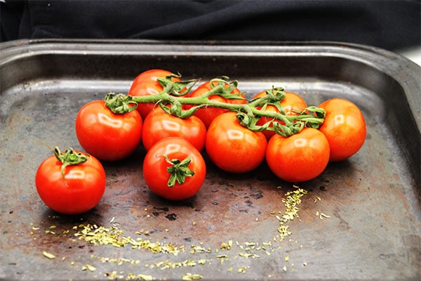Fresh tomatoes on vine and Herbs de Province on black baking tray