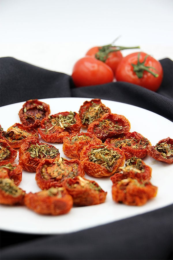oven-dried tomatoes close up on white plate with black cloth
