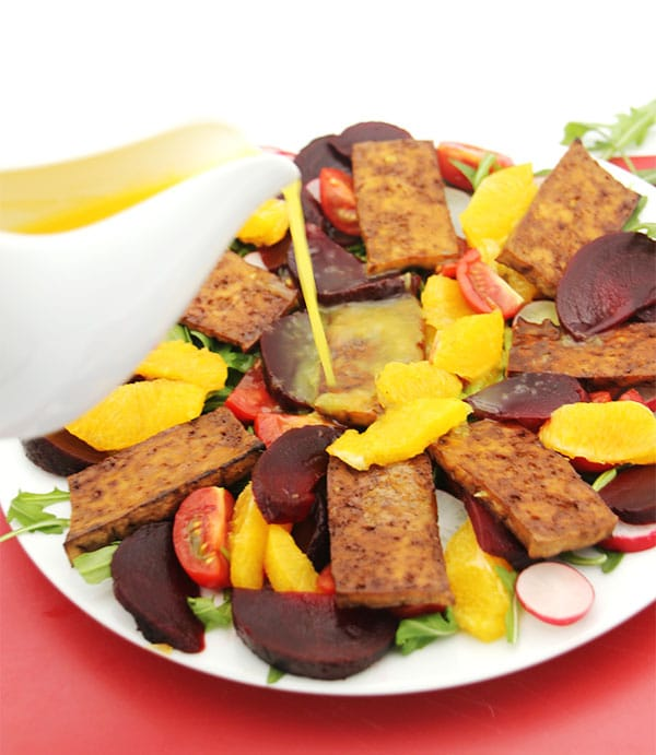 spicy beet orange tofu salad on white plate with orange dressing being poured on.