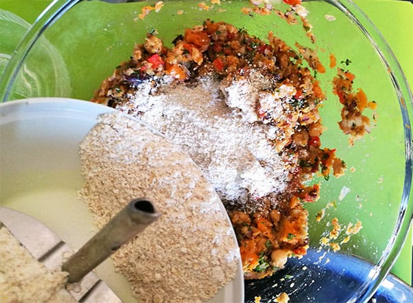 Ground oats are added to ingredients for veggie burger in glass bowl.