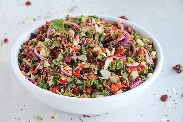 cranberry quinoa salad in big white bowl on white board with dried cranberries, almonds and quinoa