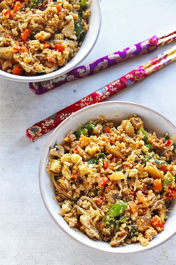 fried cauliflower rice with vegetables in 2 white bowls on white board with chopsticks on the board