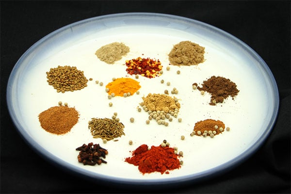 spices for Berbere spice blend on white plate with blue boarder all on black cloth.