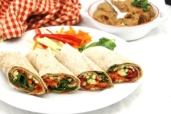 4 white bean & tomato wraps side by side on white plate.