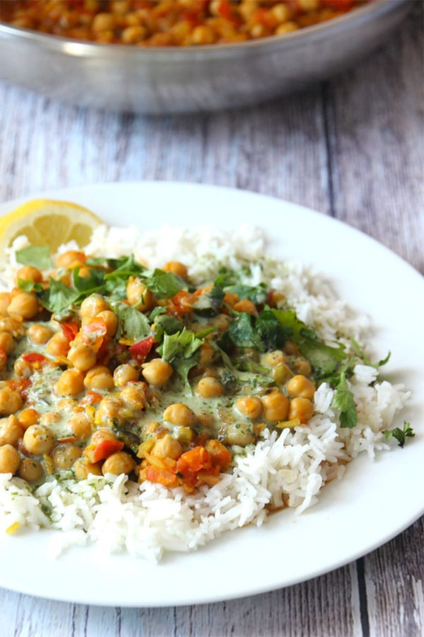 chana masala over white rice on white plate topped with coriander coconut cream and fresh coriander.