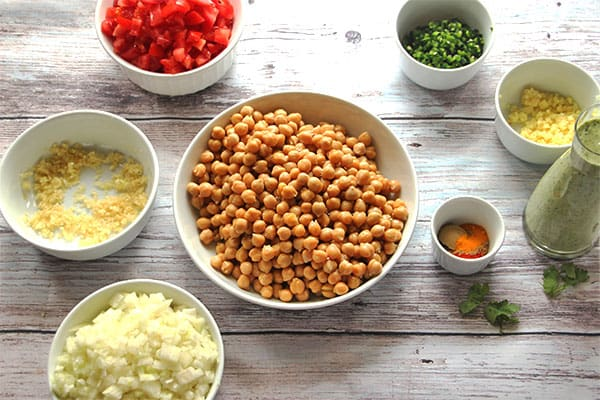 chickpeas, chopped onions, minced garlic and ginger, diced tomatoes, diced jalapenos, coriander cream and spices in white dishes on board.