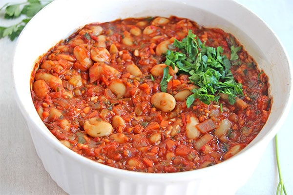 Greek baked beans (Gigantes Plaki) in white casserole dish garnished with chopped parsley.