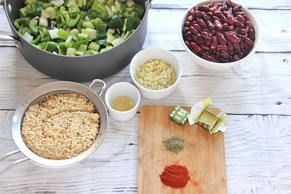 soup pot with celery, onions and peppers, bowl of red kidney beans, bowl with garlic, small bowl with apple cider vinegar, rinsed quinoa in colander, board with paprika, thyme and bouillon cube.