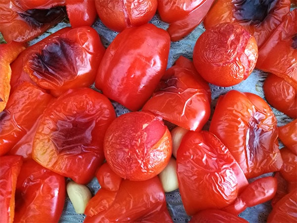Red peppers, tomatoes and garlic are roasted in the oven on a baking tray lined with parchment paper.
