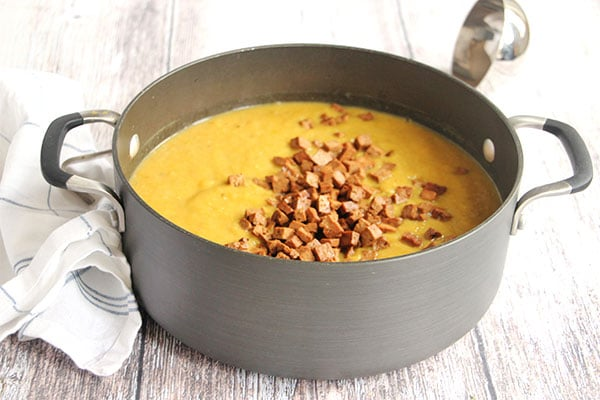 Tofu bacon cubes are added to blended smoky split pea soup.