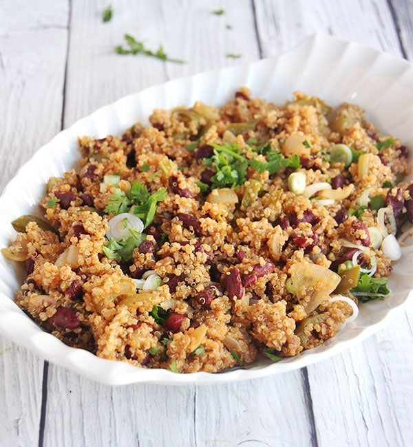 red beans and quinoa in large white dish with chopped parsley garnished on top.