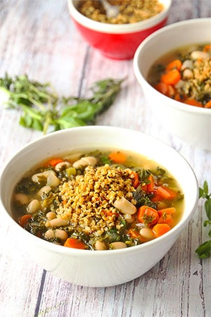 Italian white bean soup with carrots, kale and fresh herbs in white bowl with hemp Parmesan on top.